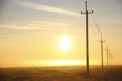 Power lines at dawn in the mist Stock Photos