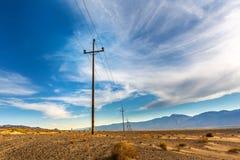 Power lines in desert valley. Stock Photo