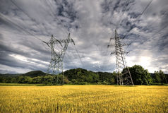 Power lines and dramatic sky. High voltage power lines above wheat field just before storm Royalty Free Stock Images