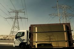 Power lines and electricity pylons reflecting in glass. Power lines reflecting in glass, carried by passing truck, in the United Arab Emirates Stock Photo
