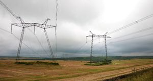 Power lines on the field in cloudy weather. Stock Photo