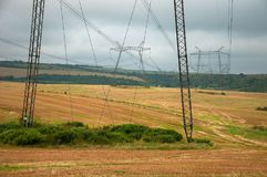 Power lines on the field in cloudy weather. Royalty Free Stock Photos