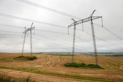Power lines on the field in cloudy weather. Royalty Free Stock Photo