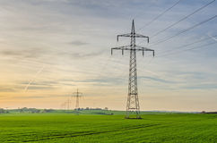 Power lines on a field during twilight Stock Images
