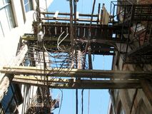 Power-lines and fire escapes in Vancouver back alley, BC, Canada royalty free stock image