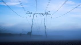 Power lines in a foggy landscape stock photos