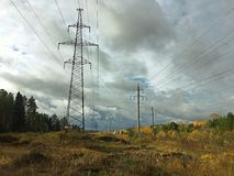 Power lines in the forest under the clouds royalty free stock image