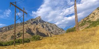Power lines on a grassy hill in Provo Canyon Utah royalty free stock photo