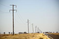 Power Lines Heat Haze. Heat haze rises as power lines blur into the distance with road in country area Stock Image