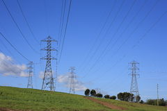 Power lines and high voltage towers. High voltage towers and transmission lines on a hill Stock Photo