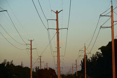Power Lines, high voltage.  Transmission towers. Three high voltage power line sets.  Sunset.  Florida.  Dusk Royalty Free Stock Photography