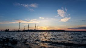 Power lines on the lake at sunset Royalty Free Stock Images