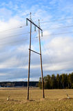 Power lines and pole. Electric high-voltage power line on cornfield Royalty Free Stock Photo