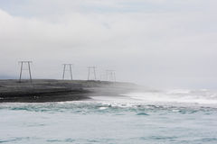 Power lines and pylons on the black shore of northern sea, Icela Royalty Free Stock Photos