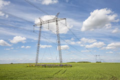 Power lines pylons next to a field Royalty Free Stock Photography