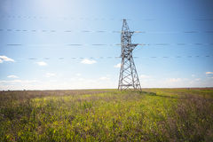 Power lines pylons next to a field Stock Photo