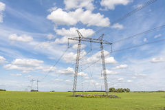 Power lines pylons next to a field Stock Images