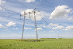 Power lines pylons next to a field Stock Photos