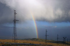 Power lines with rainbow. In cloudy sky Royalty Free Stock Image