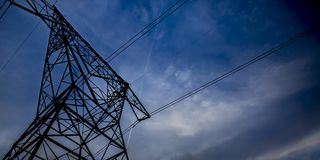 Power lines running through big scaffolding towers stock photography