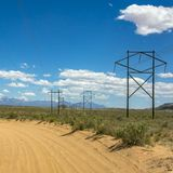 Power lines beside a sand road in Moab Utah stock image