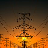 Power lines and setting sun. Royalty Free Stock Images