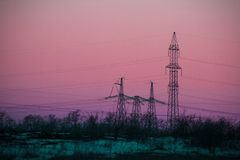 Silhouette High voltage electric tower. Power lines Silhouette High voltage electric tower on sunset time and sky on sunset time background Stock Photos
