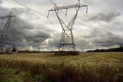 Power Lines On Stormy Afternoon. Power lines in a filed with dark rain clouds Stock Images