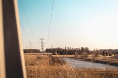Power Lines Stretching into Distance. Power Lines over beautiful fall field and pond nature industrial sky summer blue lake frozen sun sunset grass corn trees royalty free stock images