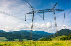 High voltage power lines tower in Carpathian mount. Power lines tower on a meadow against the blue sky. lovely energy industry background. efficient electricity Royalty Free Stock Photos