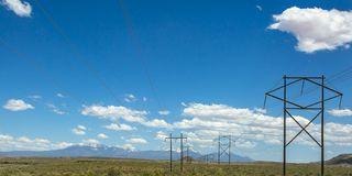 Power lines with view of mountain under blue sky royalty free stock photos