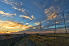 Power lines and windmills. Windmills and power lines working to supply electricty Stock Photo
