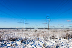 Power lines in winter snow field Royalty Free Stock Photos
