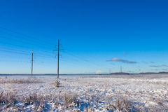 Power lines in winter snow field Royalty Free Stock Photography
