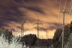 Power lines and yellow clouds at night Stock Photo