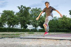 Power for Long jump. Frozen shot of a male young teenager jumping into a long jump pit Royalty Free Stock Photography