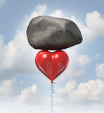 Power Of Love. Metaphor or heavy heart challenge concept as a red balloon shaped as the symbol for romance and relationships lifting up a huge rock stock illustration