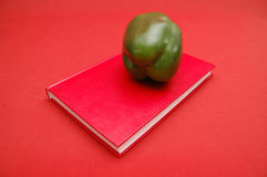 Power lunch. Red cook book with green pepper fruit on red background Stock Image