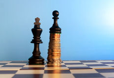 Power of the money. Concept. Chess pawn standing on the money over the king Stock Photos