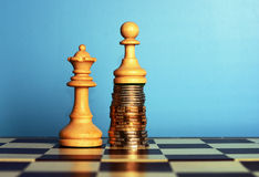 Power of the money. Concept. Chess pawn standing on the money over the queen Stock Photos