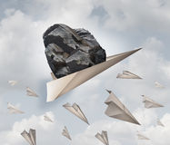 Power Of Motivation. Business success concept as a paper plane hauling a heavy rock with a group of failing origami airplanes as a metaphor for the force of Stock Photography