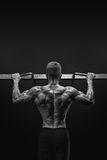 Power muscular bodybuilder guy doing pullups in gym. Fitness man. Black and white image of power muscular bodybuilder guy doing pullups in gym. Fitness man Royalty Free Stock Images