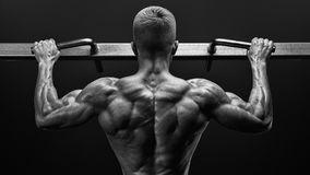 Power muscular bodybuilder guy doing pullups in gym. Fitness man. Black and white image of power muscular bodybuilder guy doing pullups in gym. Fitness man Royalty Free Stock Image