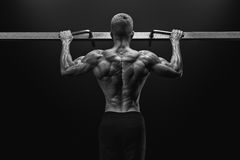 Power muscular bodybuilder guy doing pullups in gym. Fitness man royalty free stock image