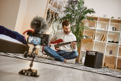 Power of music. Close up of digital camera screen with male music blogger playing electric guitar and recording new. Video for his vlog stock photography