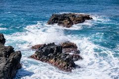 Power in nature as Atlantic Sea waves break over volcanic rocks royalty free stock photos