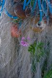 Flower growing breaking through fishing nets , floats and marine stock photography