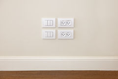 Power outlet and  light switch on the wall Stock Photos