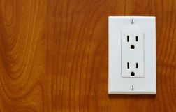 Power outlet on a wood grain surface. royalty free stock photos