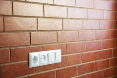 Power outlets on the brick wall / photo Royalty Free Stock Photo